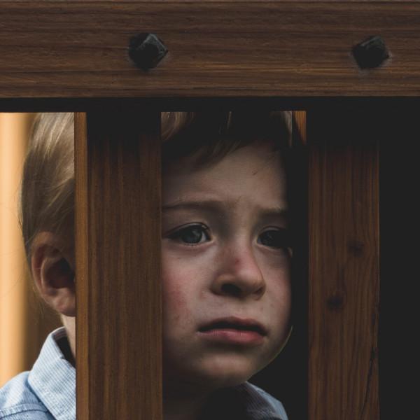 Kind mit traurigem Blick hinter Stäben